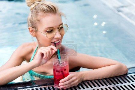 Photo pour Belle jeune femme buvant cocktail frais à bord de la piscine - image libre de droit