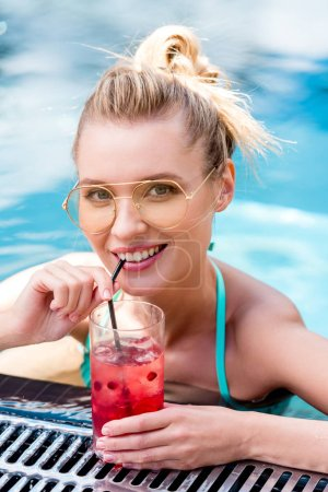 smiling young woman drinking fresh cocktail at poolside
