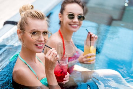 beautiful young women with delicious cocktails relaxing in swimming pool and looking at camera