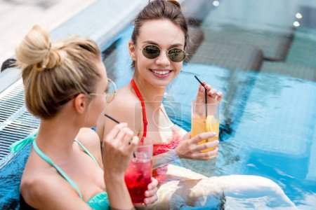 beautiful young women with delicious fruit beverages relaxing in swimming pool
