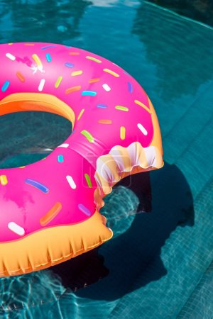 close-up shot of inflatable ring in shape of bitten donut floating in swimming pool