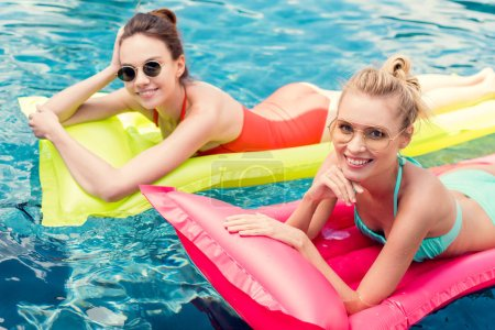 happy young women lying on inflatable mattresses in swimming pool and looking at camera