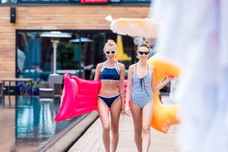 attractive young women with inflatable mattress and ring at poolside