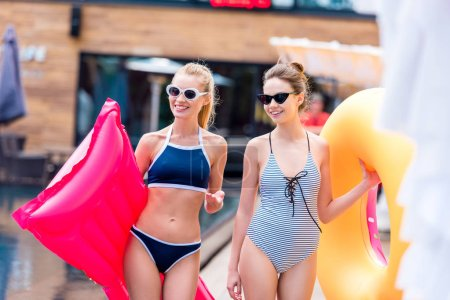 smiling young women with inflatable mattress and ring at poolside