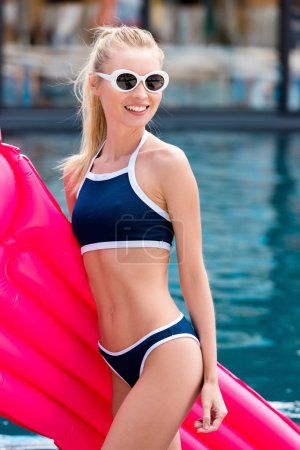smiling young woman in bikini with pink inflatable mattress looking away at poolside