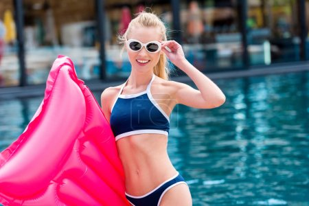 smiling young woman in bikini with pink inflatable mattress looking at camera at poolside