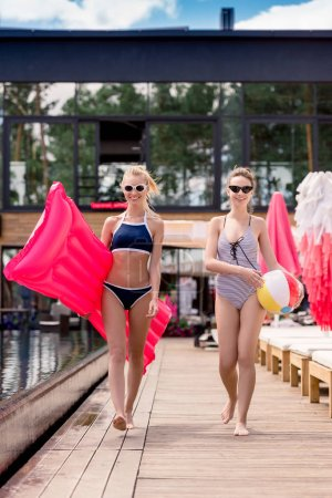 attractive young women with inflatable mattress and beach ball walking by poolside