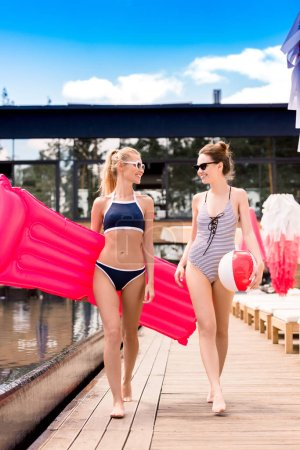 beautiful young women with inflatable mattress and beach ball walking by poolside