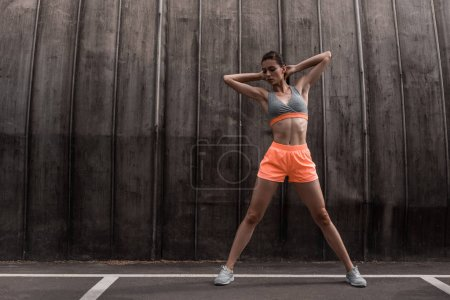 beautiful sportswoman exercising and stretching on parking