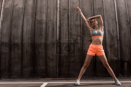 athletic woman exercising and stretching on parking