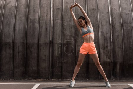 athletic woman training and stretching arms