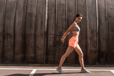 beautiful athletic woman exercising on parking