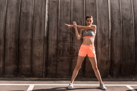 athletic woman stretching arms on parking