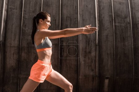 Photo for Attractive young sportswoman exercising in sportswear - Royalty Free Image