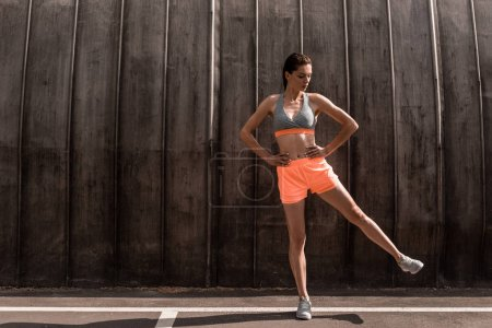 Photo for Female athlete training her legs on parking - Royalty Free Image