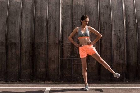 female athlete training her legs on parking
