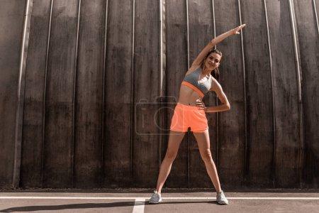 sportive girl stretching in sportswear on parking