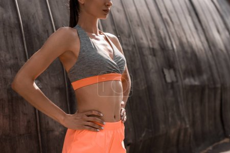cropped view of athletic woman posing in sports bra