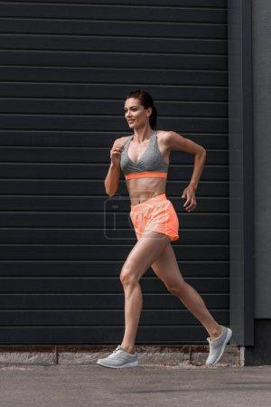 young beautiful sportswoman running in sportswear in city