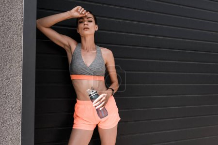 attractive sportswoman posing with fitness tracker and bottle of water