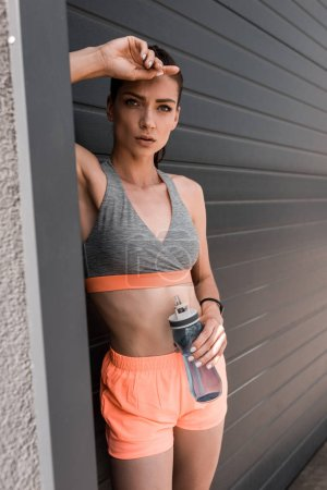 beautiful athletic woman holding sports bottle of water