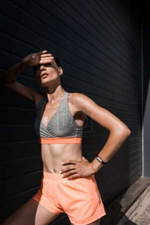 young tired sportswoman posing in sportswear with fitness tracker