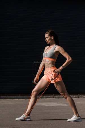 young sportswoman stretching elastic band