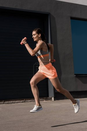 young smiling athletic woman running with dumbbells
