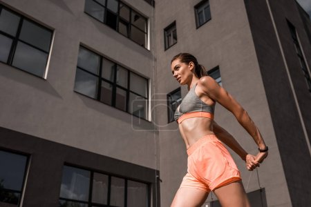 bottom view of athletic woman stretching arms in city