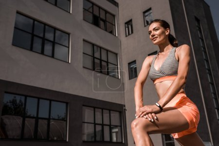 beautiful young sportswoman stretching legs in city