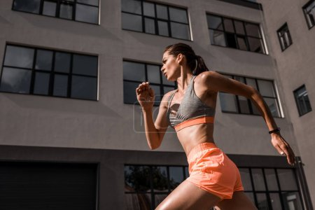 Photo for Young focused sportswoman jogging in city - Royalty Free Image
