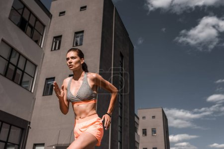 young concentrated sportswoman running with fitness tracker in city