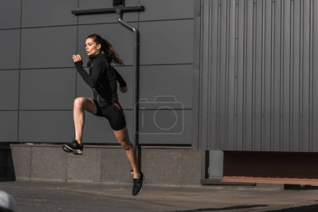 Photo for Young concentrated sportive runner training in city - Royalty Free Image