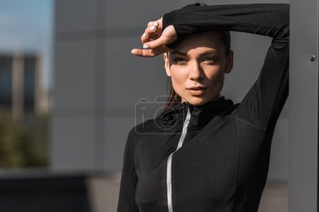 portrait of sportswoman posing in black thermal clothes