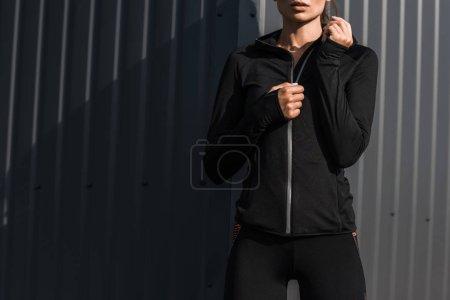 Photo pour Recadrée vue de sportive en vêtements thermiques noirs - image libre de droit