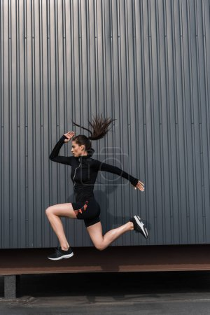 young sportswoman in black sportive thermal clothes jumping in city