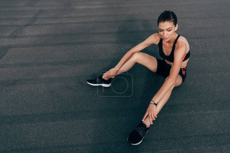 overhead view of young sportswoman with fitness tracker sitting on asphalt