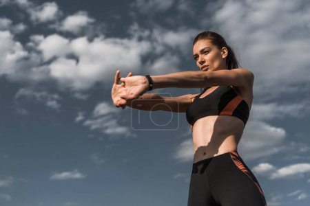 Photo for Attractive sportswoman stretching hands against blue cloudy sky - Royalty Free Image