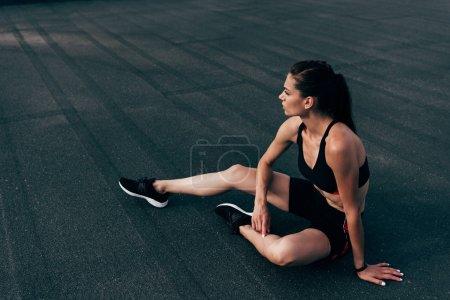 young athletic woman in sportswear sitting on asphalt