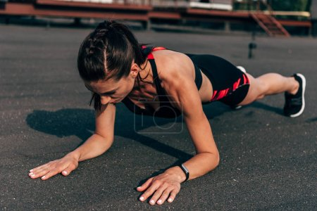 athletic woman doing plank on asphalt in city