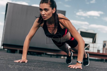 concentrated sportswoman doing push up on asphalt in city