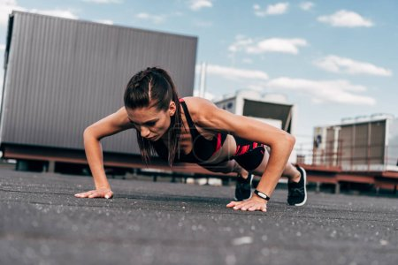 focused sportswoman doing push up on asphalt in city