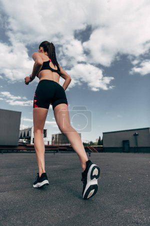 bottom view of female jogger training on roof