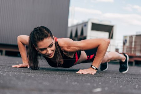 young smiling sportswoman doing push up on asphalt in city