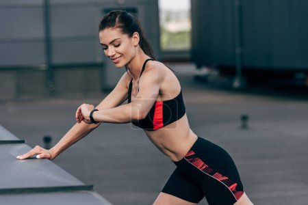 young smiling sportswoman looking on fitness tracker and doing push up on roof