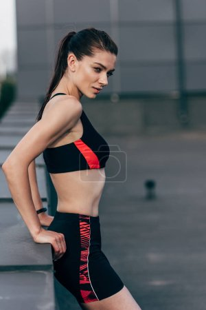 young attractive sportswoman posing in sportswear on roof