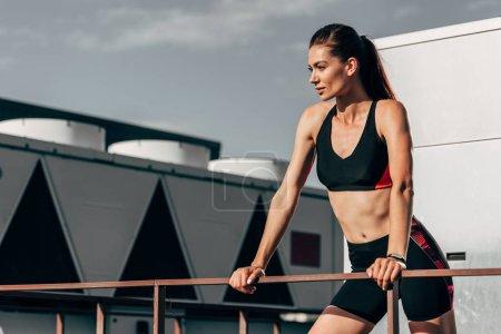 beautiful young sportswoman posing in sportswear on roof