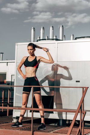 young sportswoman in sportswear holding ponytail and posing on roof