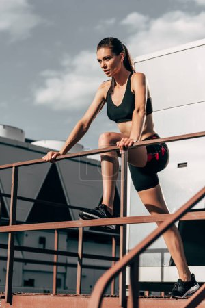Photo pour Axé sur une femme athlétique en due forme sportswear sur toit - image libre de droit