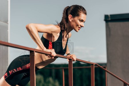 young sportswoman exercising and doing push up at railings on roof